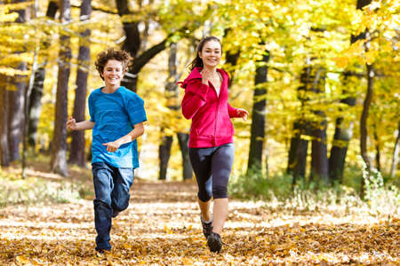 Girl and boy running, jumping in park Stock Photo - 23804793