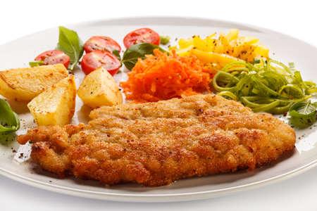 schnitzel: Pork chop, baked potatoes and vegetable salad