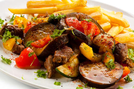 Grilled meat with French fries and vegetables photo
