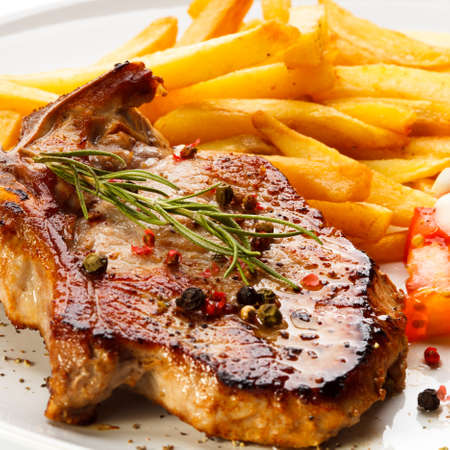 loin chops: Grilled steaks, chips and vegetables