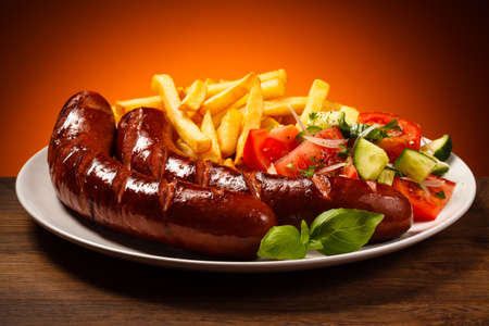 grilled sausages: Grilled sausages, French fries and vegetables