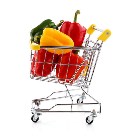 Shopping trolley full of pepper on white  photo