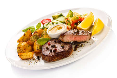 Grilled steaks, baked potatoes and vegetables photo