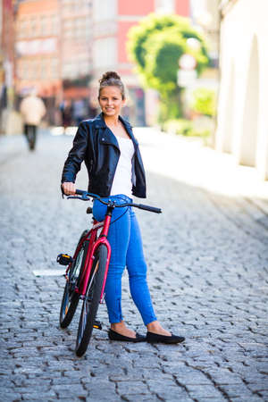 Urban biking - young woman and bike in city photo