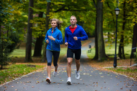 Healthy lifestyle - woman and man running in park photo