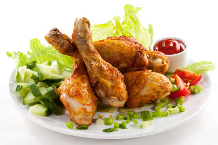 Grilled chicken legs and vegetables on white background photo