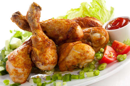 appetizers menu: Grilled chicken legs and vegetables on white background