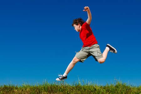 Boy jumping, running against blue sky photo