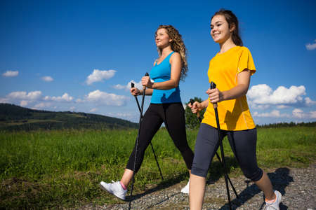 walking: Nordic walking - active people working out outdoor