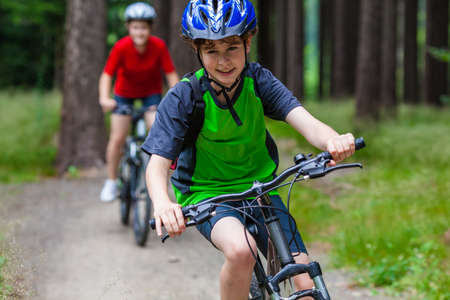 woman bike: Healthy lifestyle - teenage girl and boy biking Stock Photo