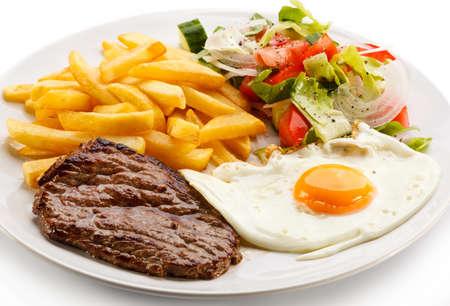 Gegrilde biefstuk, frietjes, gebakken ei en groenten Stockfoto