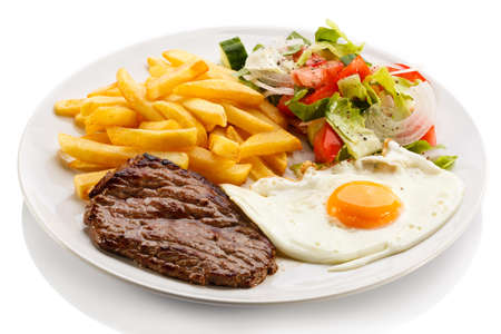Grilled steaks, French fries, fried egg and vegetables photo