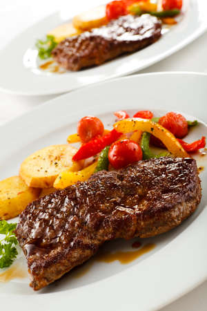 Grilled beefsteak, baked potatoes and vegetables photo