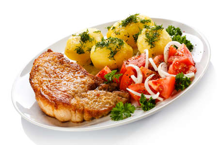 pork chop: Grilled steaks, boiled potatoes and vegetable salad Stock Photo