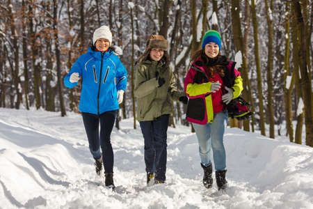 Active family - mother and kids running in winter park photo