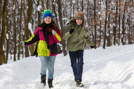 Girl and boy running in winter park photo