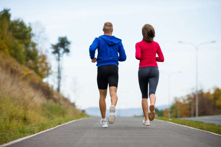 action girl: Healthy lifestyle - woman and man running in park