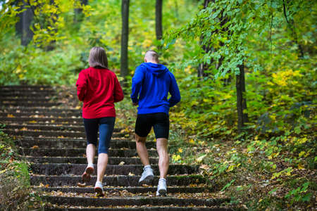 stair: Healthy lifestyle - woman and man running in park