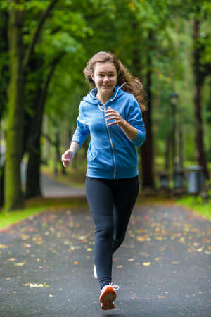 jogging track: Young woman running in city park Stock Photo