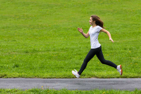 Young woman running in city park Stock Photo - 25628005