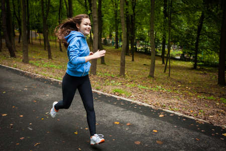 Young woman running in city park photo