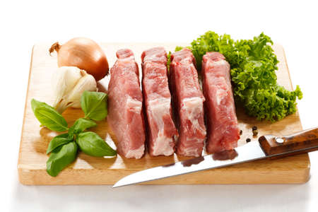 beef meat: Raw pork on cutting board and vegetables