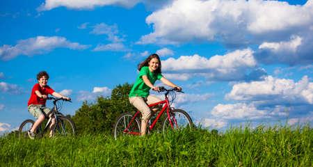 Healthy lifestyle - teenage girl and boy biking photo