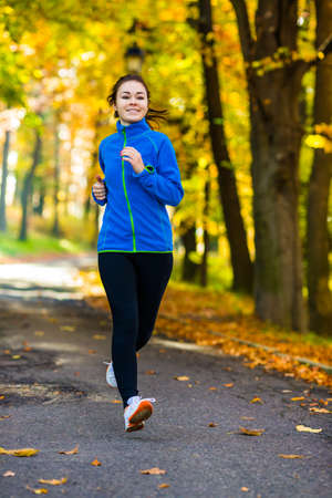 Young woman running in autumn park photo