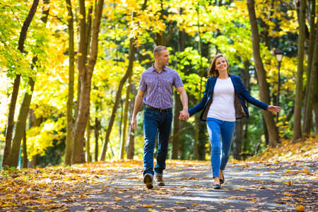 front of: Urban leisure - woman and man walking in park Stock Photo