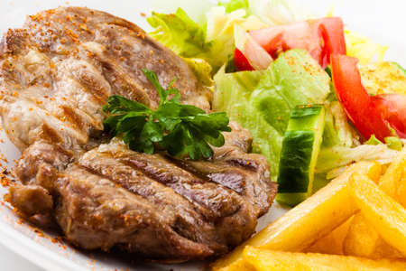 dinner plate: Grilled steak, French fries and vegetables Stock Photo