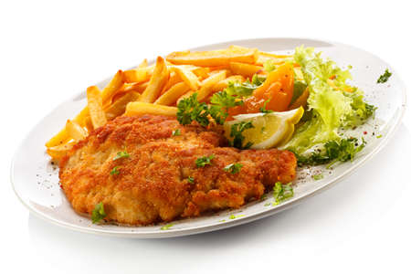 Pork chop, French fries and vegetables Stock Photo