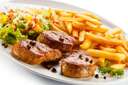 Grilled steaks served with french fries and vegetables on a plate