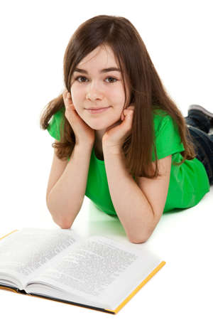 laying down: Girl lying down on the floor with a book Stock Photo