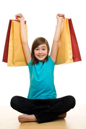 Girl sitting cross legged while holding shopping bags