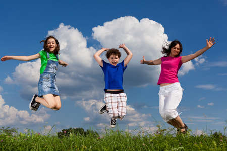 daugther: Mother and children jumping in the air outdoors