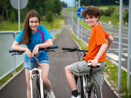 Boy and girl on their bicycles photo