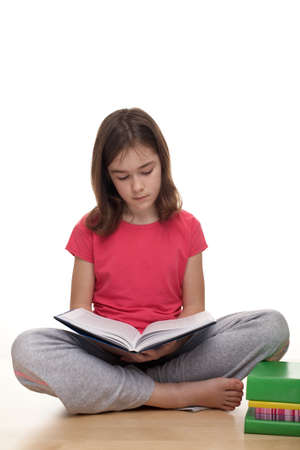 Young girl reading a book while sitting on the floor