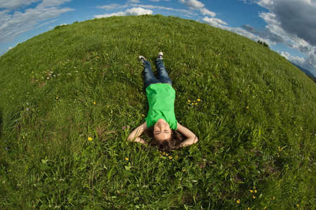 lying on grass: A young girl lying down on the grass