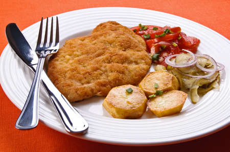 pork chop: Fried chop pork served with potatoes and vegetables on a plate