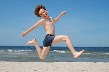 Junge, der am Meer springt