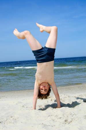Junge am Meer macht einen Handstand