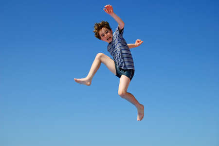 hopping: Young boy jumping at the seaside Stock Photo