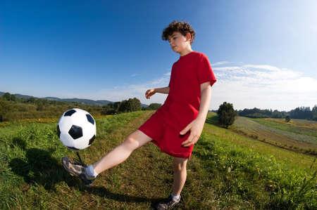 boy ball: A young boy kicking a football