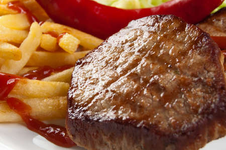 Grilled steak served with french fries and vegetables photo