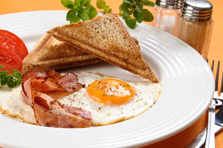 Breakfast set consisting of toasts, egg, bacon and vegetables photo