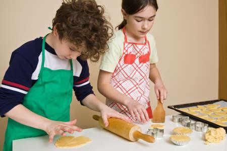 baking cookies: Giovane ragazzo e una ragazza cuocere i biscotti