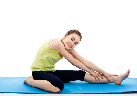 Girl sitting and stretching on yoga mat Standard-Bild