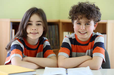 cross arms: Boy and girl smiling at camera in classroom