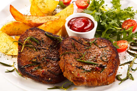 Grilled steak with wedges and salad Stock Photo