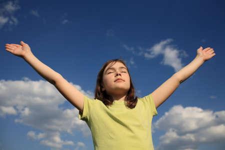 Girl raising up hands against blue sky
